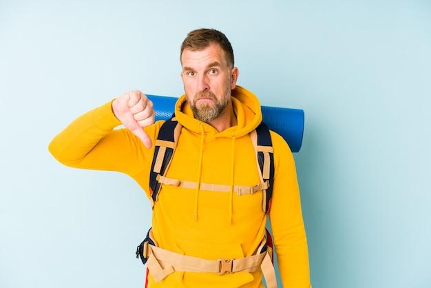 Senior wandelaar man geïsoleerd op blauwe muur met een afkeer gebaar, duimen naar beneden. meningsverschil concept.