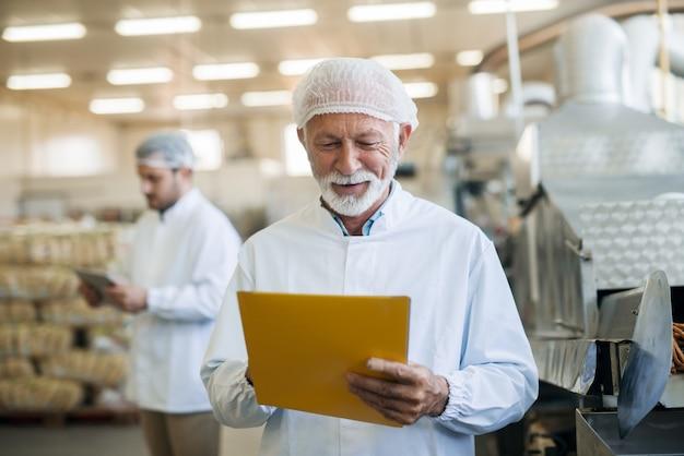Senior werknemer controleren documentatie terwijl staande in voedselfabriek. beschermend uniform aan.