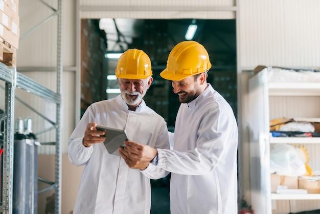 Senior werknemer tonen aan collega documenten op tablet. magazijn interieur.