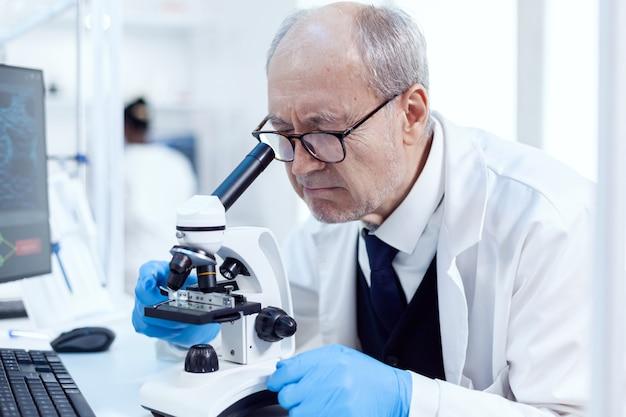 Senior wetenschapper bezig met druk laboratorium met behulp van moderne microscoop met dia's. chemicus-onderzoeker in steriel laboratorium die experimenten doet voor de medische industrie met behulp van moderne technologie.
