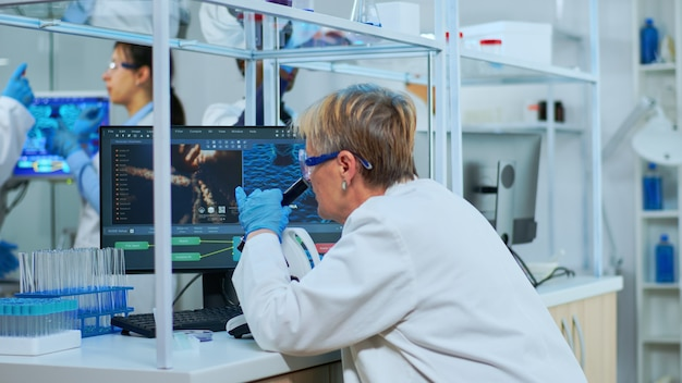 Senior wetenschapper die door een microscoop kijkt in een modern uitgerust laboratorium. multi-etnisch team onderzoekt virusevolutie met behulp van hightech voor wetenschappelijk onderzoek naar vaccinontwikkeling tegen covid19.
