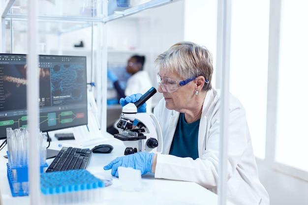 Senior wetenschapper die medische analyse en techniek doet met behulp van een microscoop. oudere onderzoeker die wetenschappelijk onderzoek uitvoert in een steriel laboratorium met behulp van een moderne technologie.