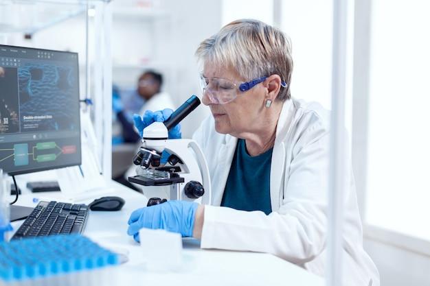Senior wetenschapper die wetenschappelijk experiment met microscoop uitvoert. oudere onderzoeker die wetenschappelijk onderzoek uitvoert in een steriel laboratorium met behulp van een moderne technologie.