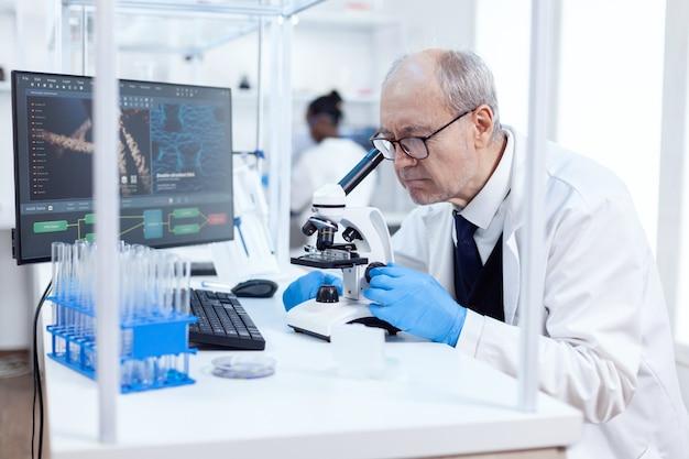 Senior wetenschapper in chemisch laboratorium gebruikt microscoop die aan nieuwe geneeskunde werkt. chemicus-onderzoeker in steriel laboratorium die experimenten doet voor de medische industrie met behulp van moderne technologie.