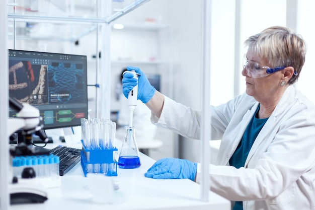 Senior wetenschapper vrouw nemen monster uit glazen kolf met behulp van moleculaire pipet. mensen in innovatief farmaceutisch laboratorium met moderne medische apparatuur voor genetisch onderzoek.