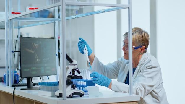 Senior wetenschapper vrouw pipetteren vloeistof naar reageerbuis in modern uitgerust lab. multi-etnisch team onderzoekt virusevolutie met behulp van hightech voor wetenschappelijke analyse van behandelingsontwikkeling tegen covid19
