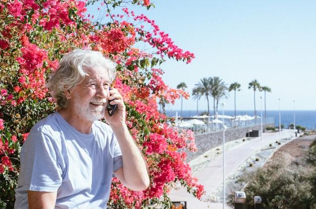 Senior witharige man zit buiten op zee met behulp van mobiele telefoon. horizon boven water. roze bloeiende plant aan de zijkant. gezonde levensstijl, rustig pensioen