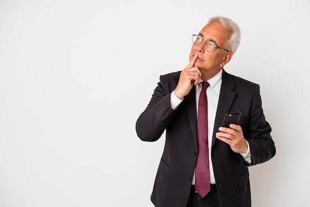 Senior zakelijke amerikaanse man met mobiele telefoon geïsoleerd op een witte achtergrond zijwaarts kijkend met twijfelachtige en sceptische uitdrukking.