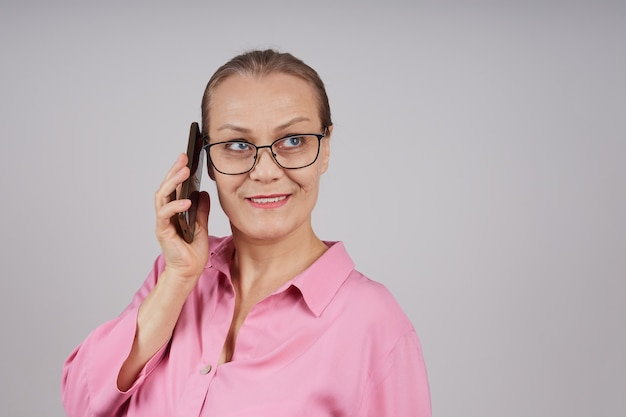 Senior zaken vrouw in glazen, in een roze blouse praten over een mobiele telefoon. geïsoleerde foto op een grijze achtergrond.