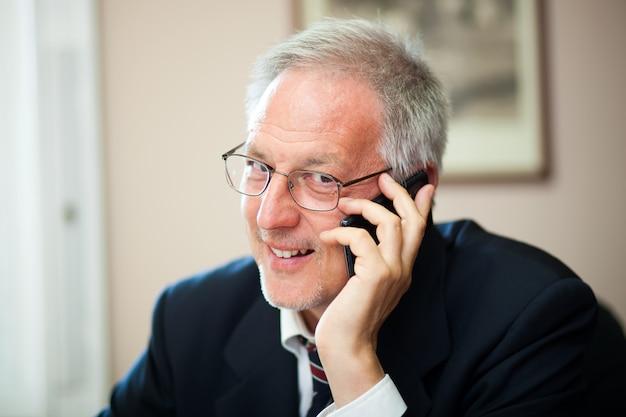 Senior zakenman aan de telefoon