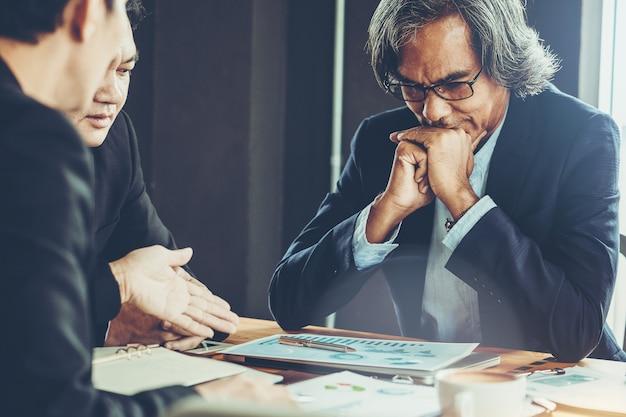 Senior zakenman als baas in vergadering en bespreken voor de situatie op de beurs.