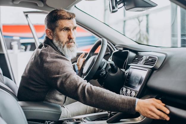 Senior zakenman die een auto kiest in de autoshowroom