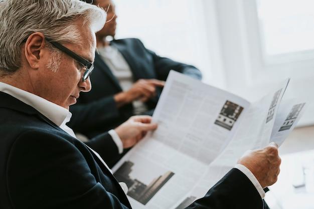 Senior zakenman die een krant leest