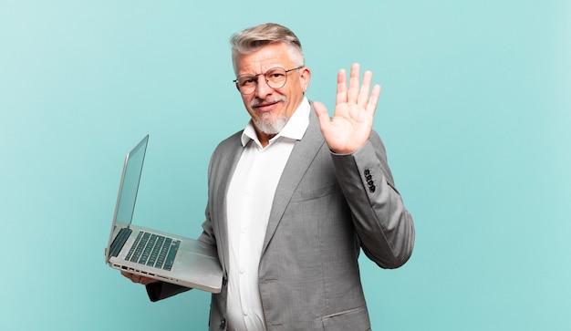 Senior zakenman die gelukkig en opgewekt glimlacht, met de hand zwaait, u verwelkomt en begroet, of afscheid neemt
