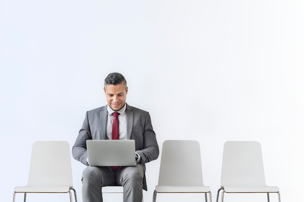 Senior zakenman die op een laptop in de kamer werkt