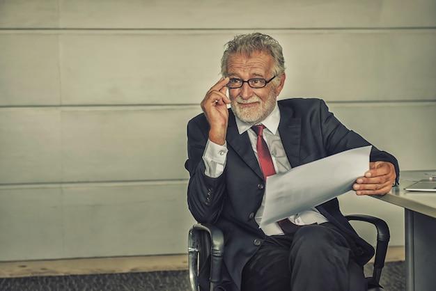 Senior zakenman die op kantoor werkt. kijkend naar de bedrijfswinstgrafiek op papier.