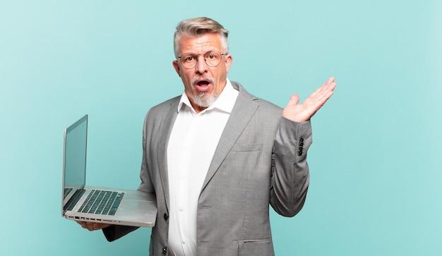 Senior zakenman die verrast en geschokt kijkt, met open mond terwijl hij een object vasthoudt met een open hand aan de zijkant