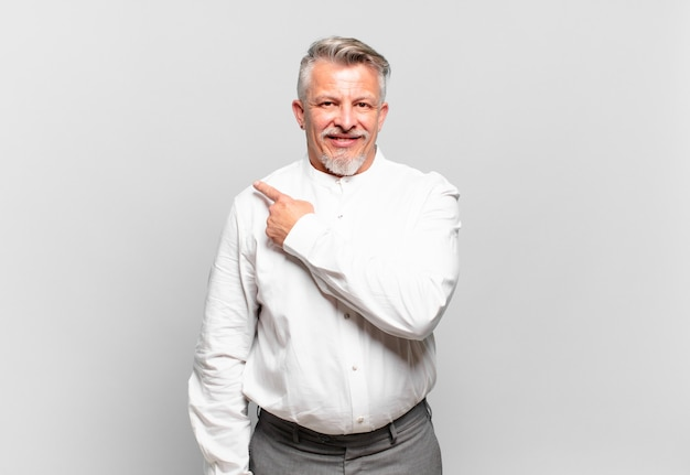 Senior zakenman die vrolijk lacht, zich gelukkig voelt en naar de zijkant en naar boven wijst, een object in de kopieerruimte laat zien