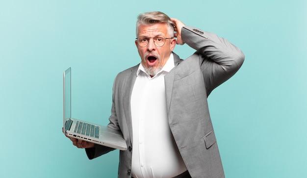 Senior zakenman die zich gestrest, bezorgd, angstig of bang voelt, met de handen op het hoofd, in paniek bij vergissing