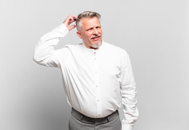 Senior zakenman die zich verward en verward voelt, hoofd krabt en opzij kijkt