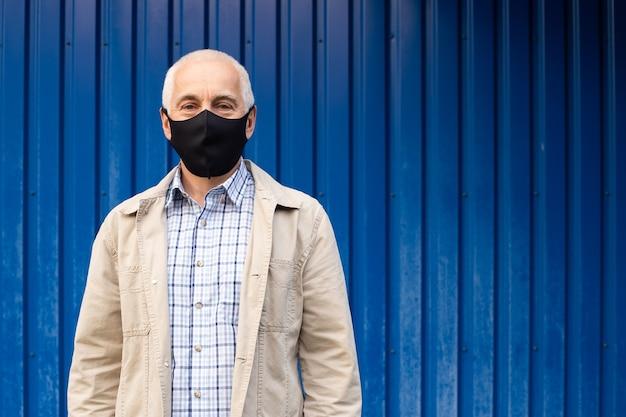 Senior zakenman draagt beschermend masker tegen infectieziekten en griep op blauw