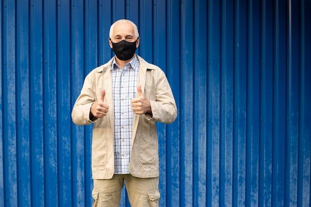 Senior zakenman draagt een beschermend masker en geeft duimen op