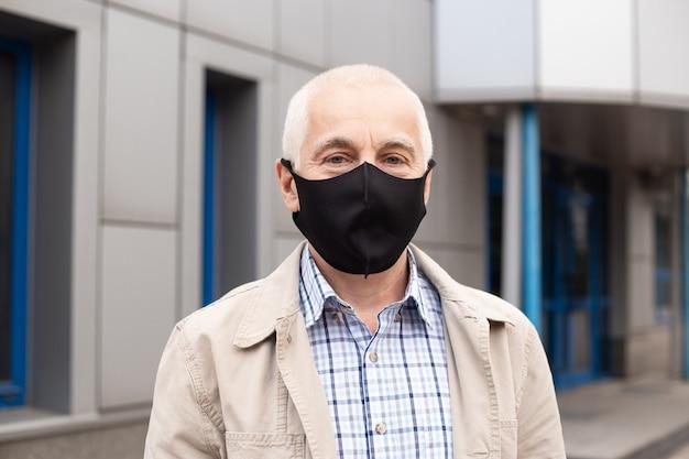 Senior zakenman draagt een beschermend masker