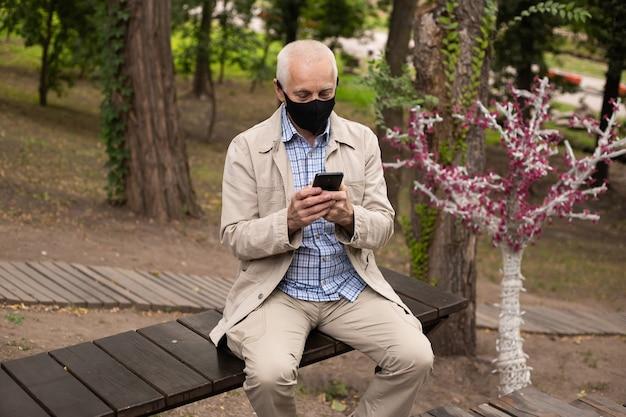 Senior zakenman dragen masker met smartphone in park