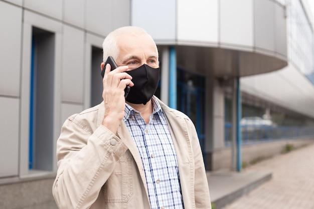 Senior zakenman dragen masker praten met smartphone in stad in de buurt van kantoorgebouwen