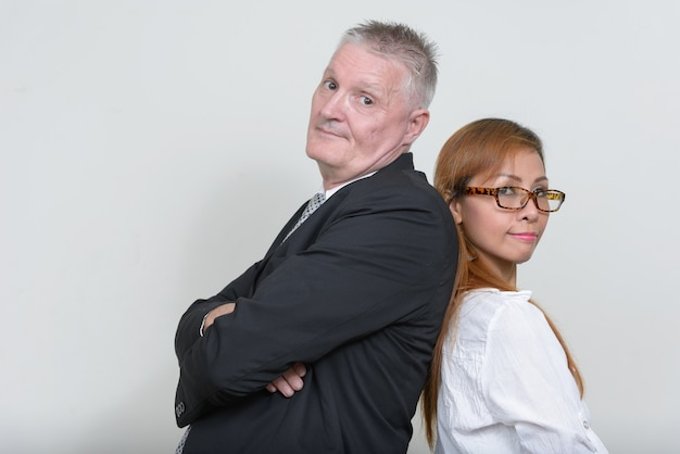 Senior zakenman en volwassen aziatische zakenvrouw samen tegen wit