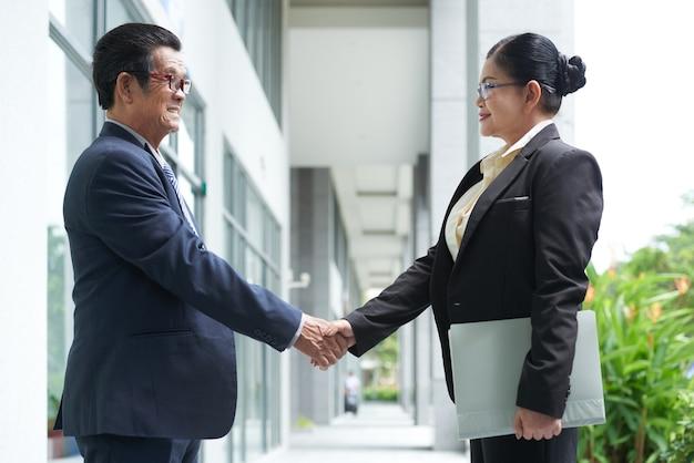 Senior zakenman en zakenvrouw kijken elkaar aan en schudden elkaar de hand voordat ze over een fusie onderhandelen