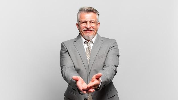 Senior zakenman glimlachend gelukkig met vriendelijke, zelfverzekerde, positieve blik, aanbieden en tonen van een object of concept