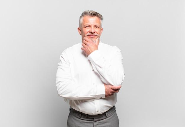 Senior zakenman glimlachend met een gelukkige, zelfverzekerde uitdrukking met de hand op de kin, zich afvragend en opzij kijkend
