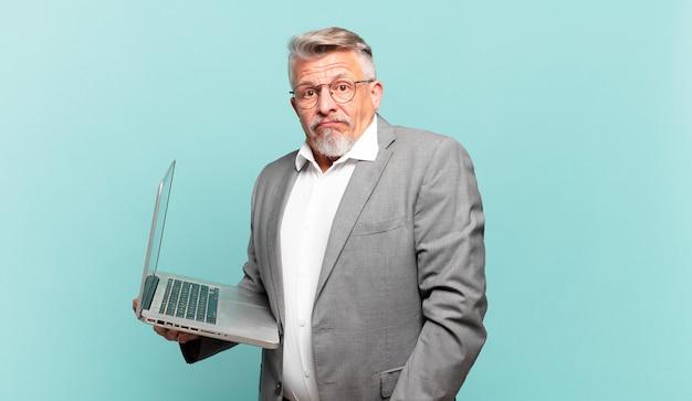 Senior zakenman haalt zijn schouders op, voelt zich verward en onzeker, twijfelt met gekruiste armen en kijkt verbaasd