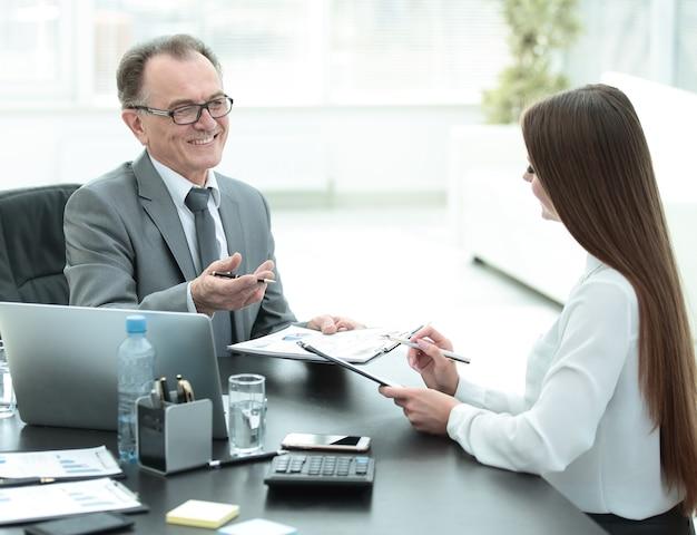 Senior zakenman in gesprek met zijn jonge assistent aan de balie