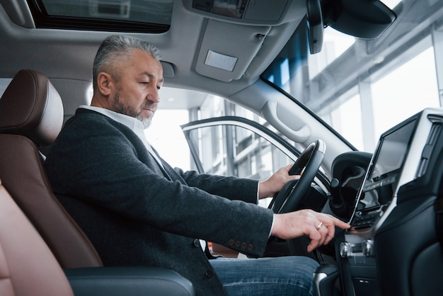 Senior zakenman in officiële kleding zit in een luxeauto en het indrukken van de knoppen op de muziekspeler