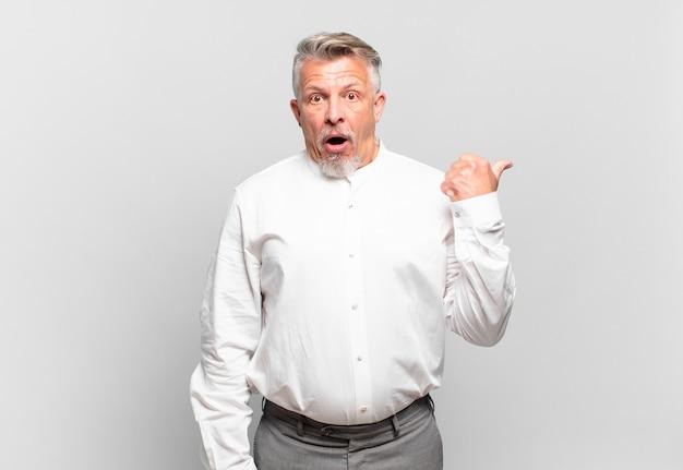 Senior zakenman kijkt verbaasd in ongeloof, wijst naar een object aan de zijkant en zegt wow, ongelooflijk