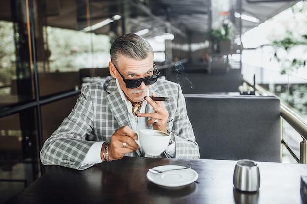 Senior zakenman koelen op zomerterras met een kopje koffie