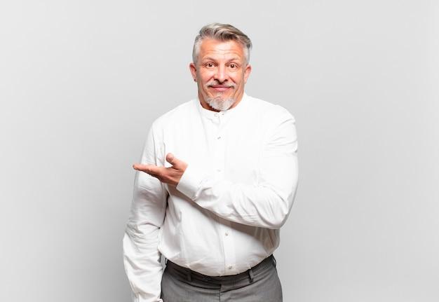 Senior zakenman lacht vrolijk, voelt zich gelukkig en toont een concept in kopieerruimte met handpalm