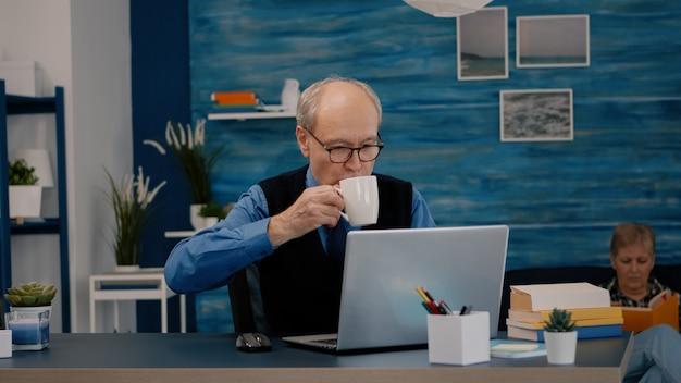 Senior zakenman leest rapporten voor laptop die thuis werkt en koffie drinkt. gepensioneerde man die moderne technologie gebruikt om typen te analyseren terwijl zijn vrouw op de bank zit en een boek leest