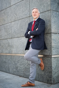 Senior zakenman liggend tegen een muur in een stad