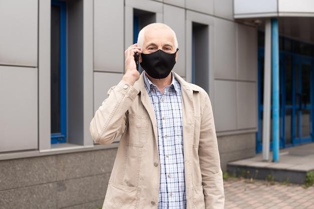 Senior zakenman masker dragen tijdens het bellen met smartphone