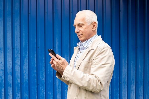 Senior zakenman met behulp van smartphone op blauwe achtergrond, copyspace. senior man, moderne technologie