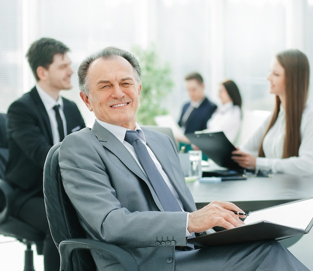 Senior zakenman met een klembord op de achtergrond van de office.photo met kopieerruimte