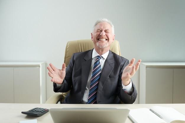 Senior zakenman met kieskeurige glimlach