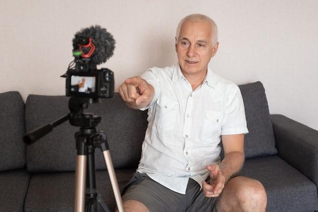 Senior zakenman motivatie spreker video maken voor blog met videocamera