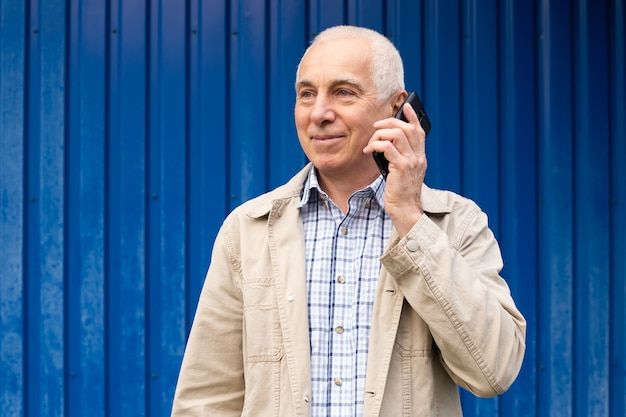 Senior zakenman praten met smartphone op blauwe achtergrond, copyspace. senior man, moderne technologie