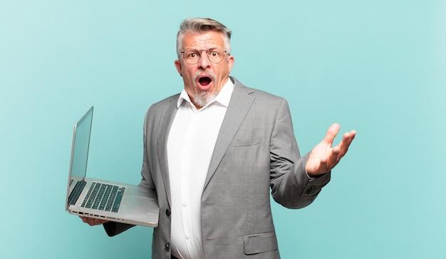 Senior zakenman voelt zich extreem geschokt en verrast, angstig en in paniek, met een gestresste en geschokte blik