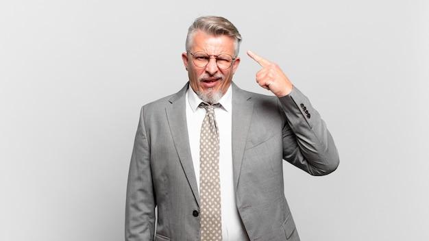 Senior zakenman voelt zich verward en verbaasd en laat zien dat je gek, gek of gek bent