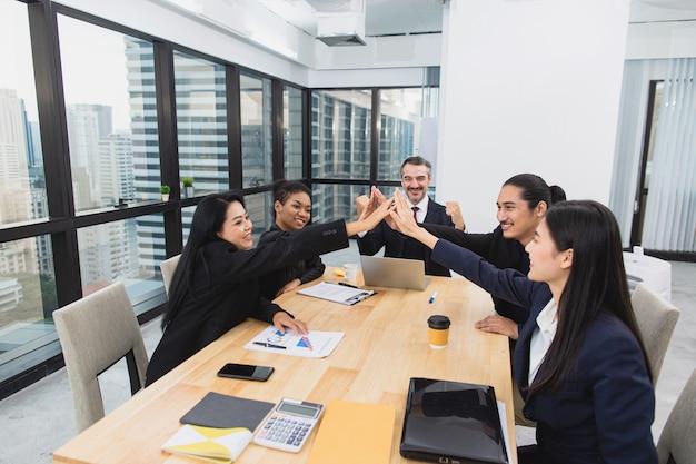 Senior zakenman vrolijkt op en geeft high five met aziatische collega in vergaderruimte op kantoor
